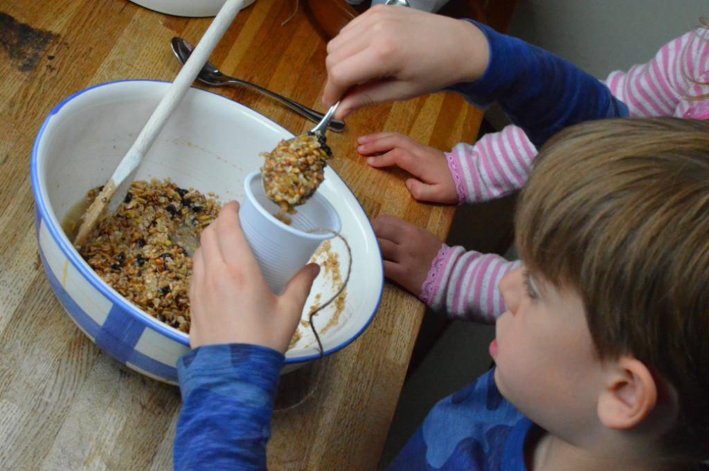 spooning bird seed mixture into pot