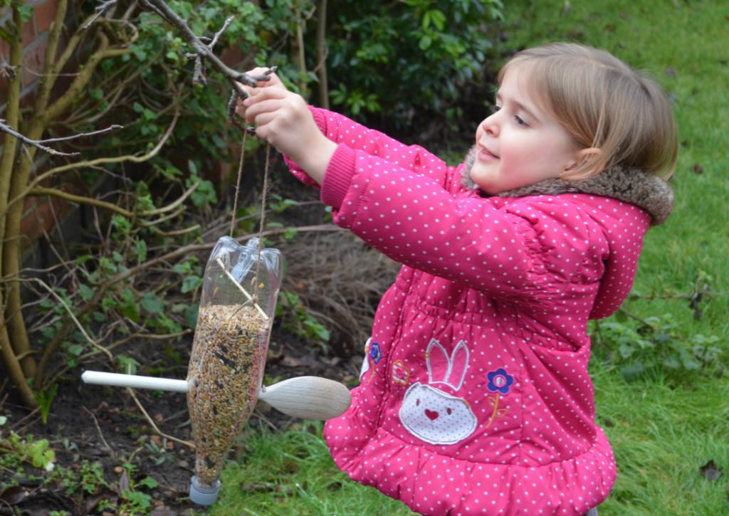 hanging up a homemade bird feeder in the garden