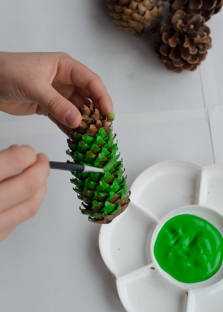 painting pine cones with green paint