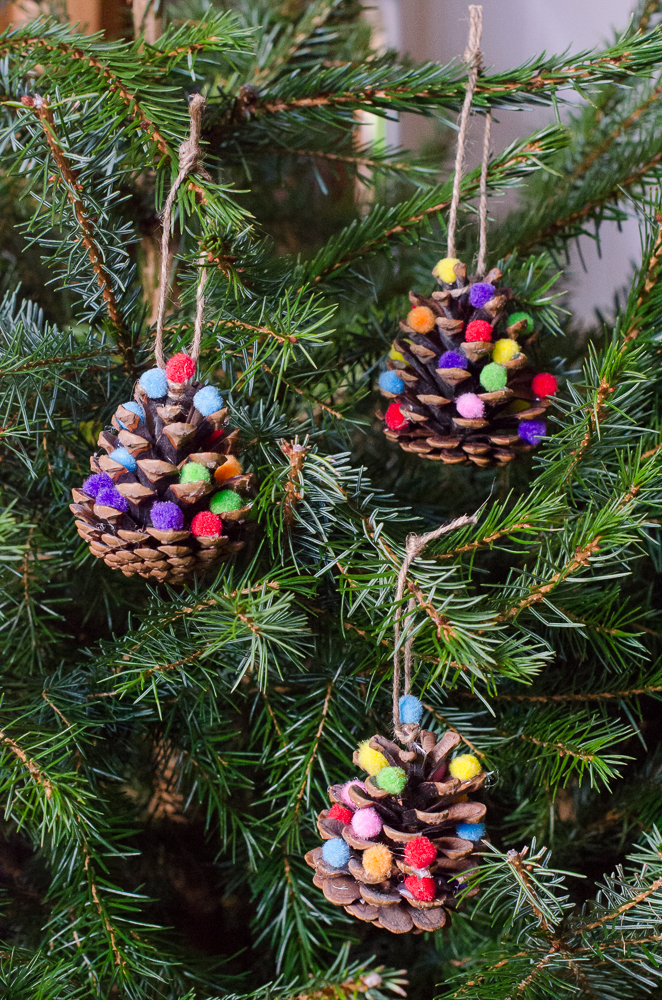 homemade Christmas decorations made from pine cones and mini pom poms