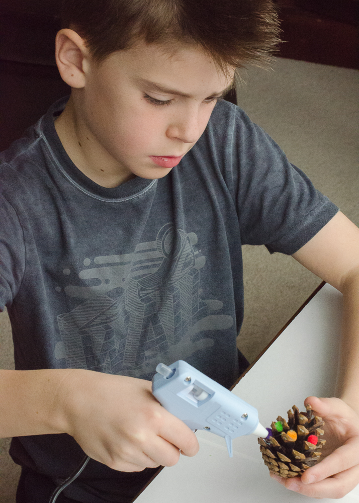 child using a hot glue gun to stick mini pom poms onto pine cones