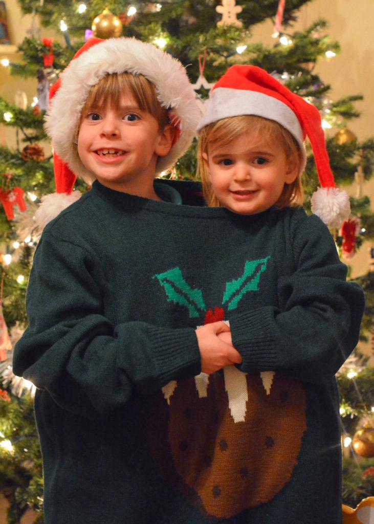 two children inside one Christmas jumper