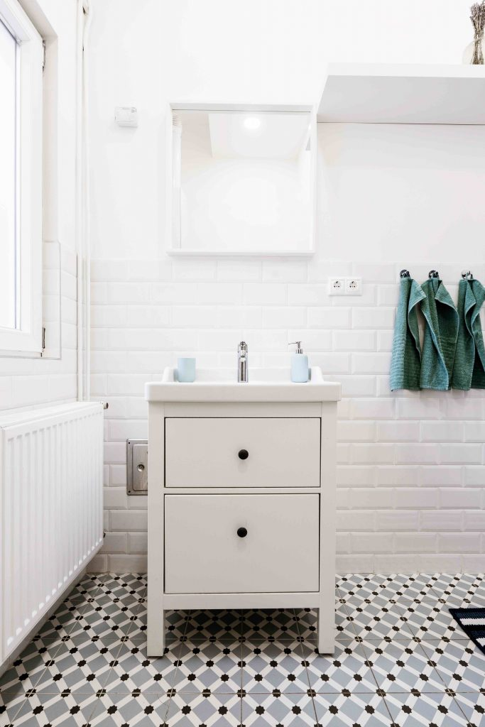 white tiled bathroom sink with mirror
