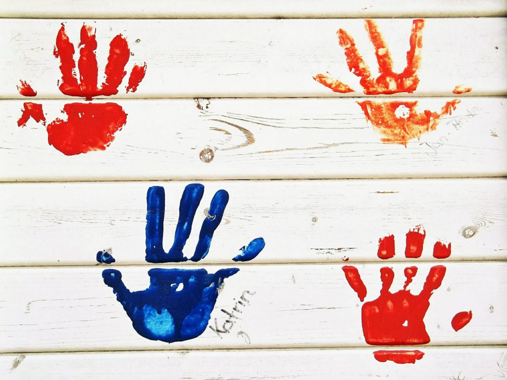children's handprints on white wooden board