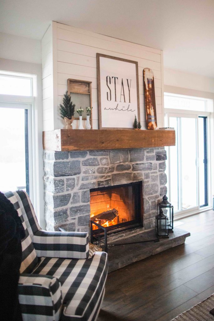 rustic interior design - stone fireplace with wooden mantel