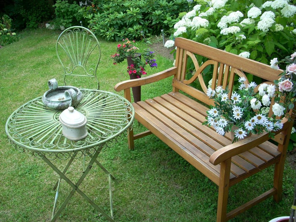 garden bench next to aged metal table and chair