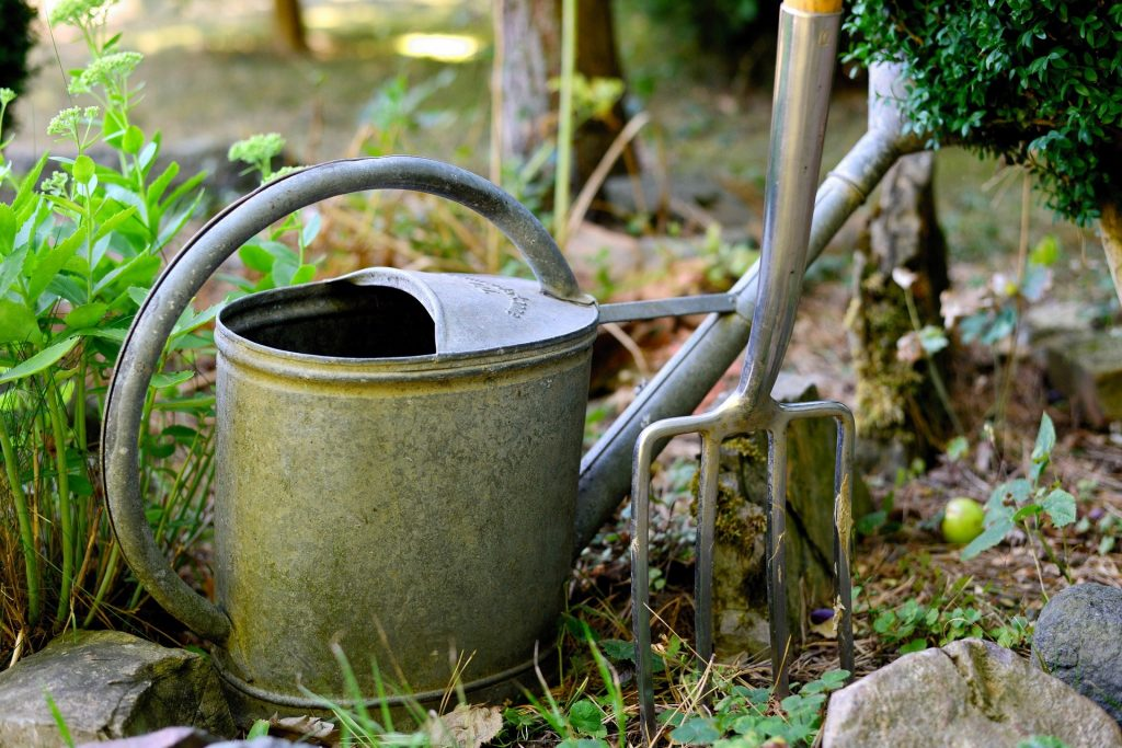 metal garden watering can and fork