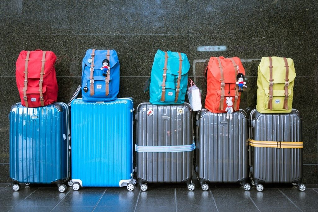 row of suitcases with backpacks balanced on top