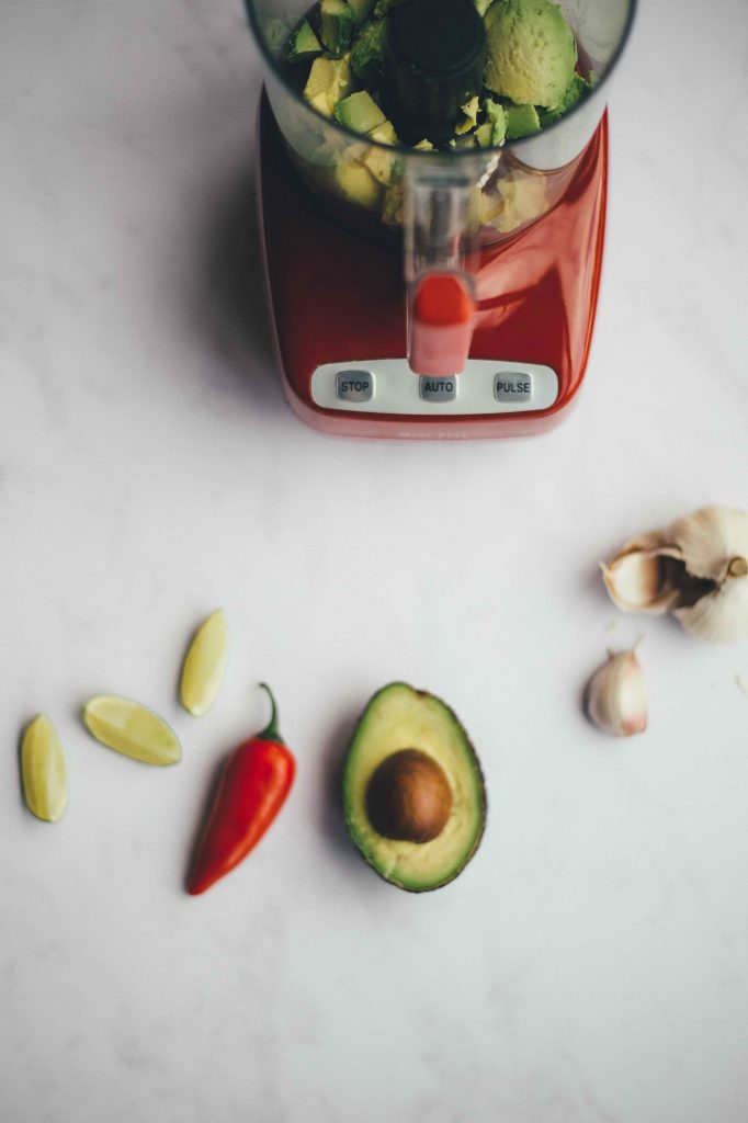 food processor with avocado, chilli, lime and garlic