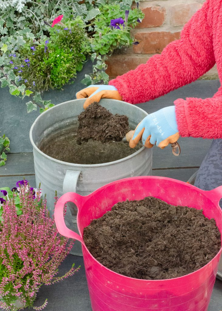 adding compost to container
