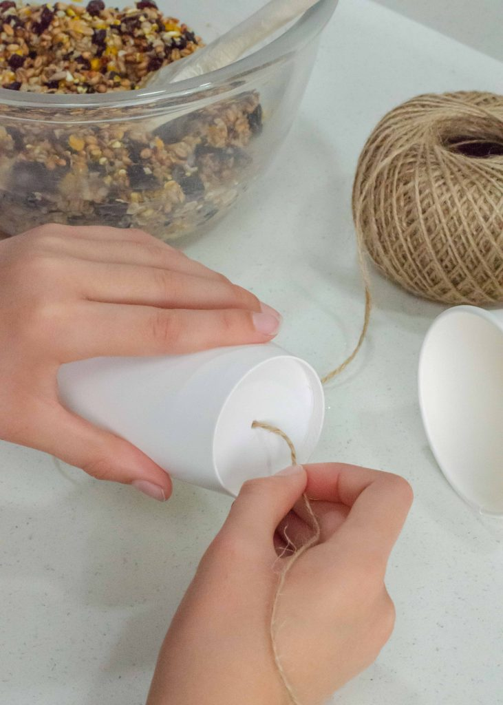 threading string through the bottom of a paper cup to make homemade bird feeders