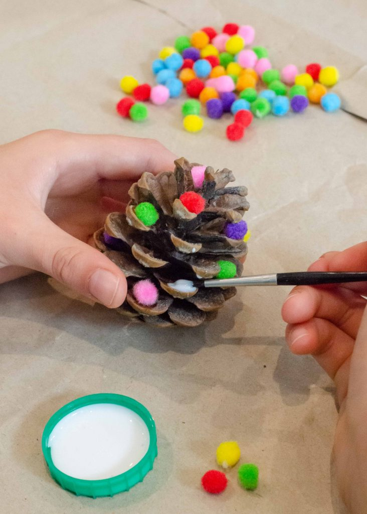 making homemade christmas decorations using pine cones and mini pom poms