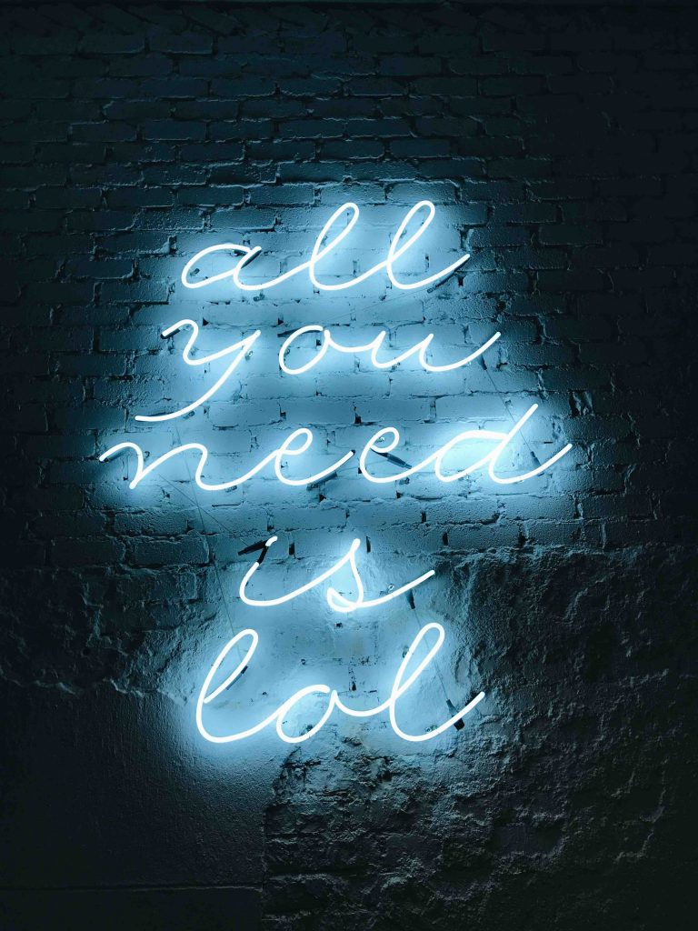 neon sign saying all you need is lol