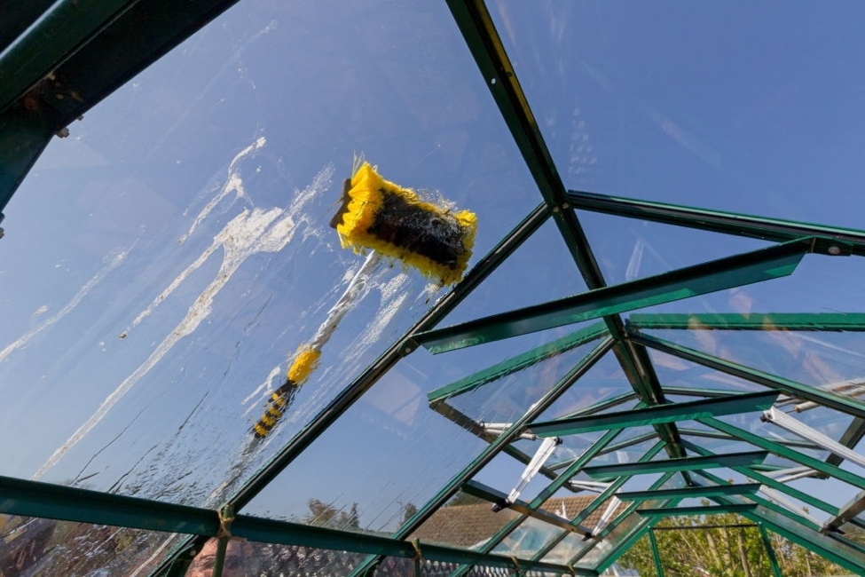 brush being used to clean greenhouse panels