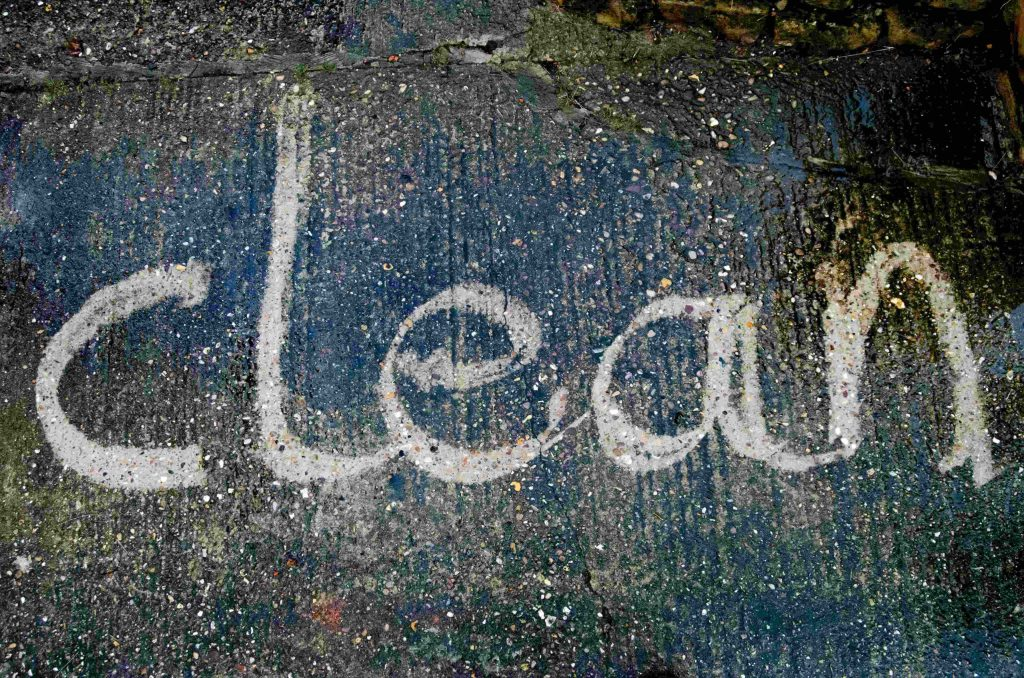 the word 'clean' written in dirt on concrete