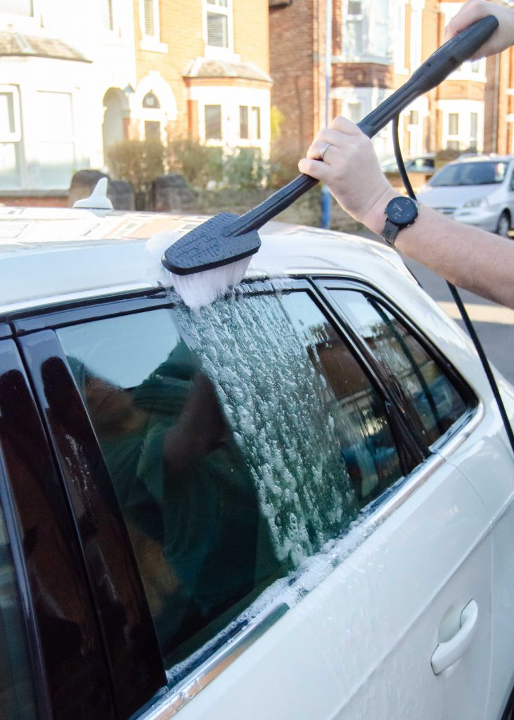 using a pressure washer with brush attachment to clean a car