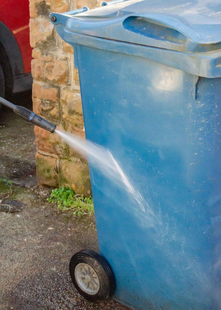 using a pressure washer to clean a wheelie bin