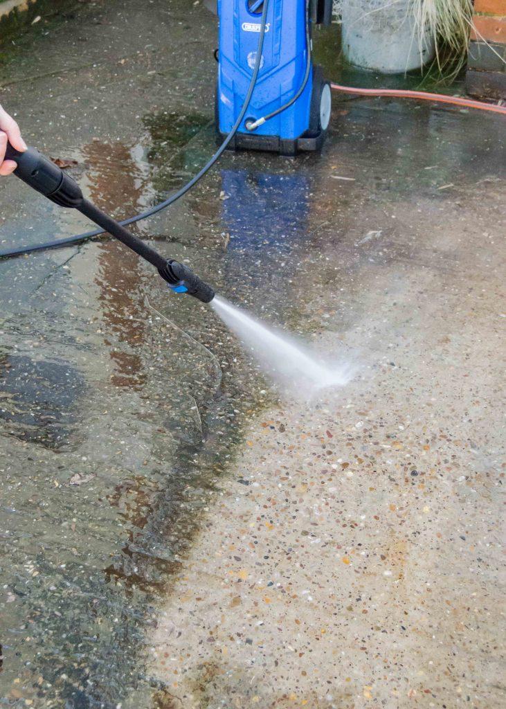 using a draper pressure washer to clean a drive