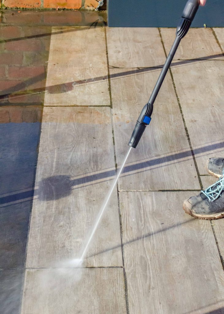 using a pressure washer to clean a patio