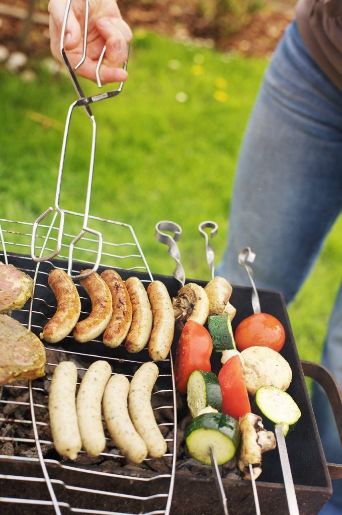 sausages and vegetable kebabs on a barbecue