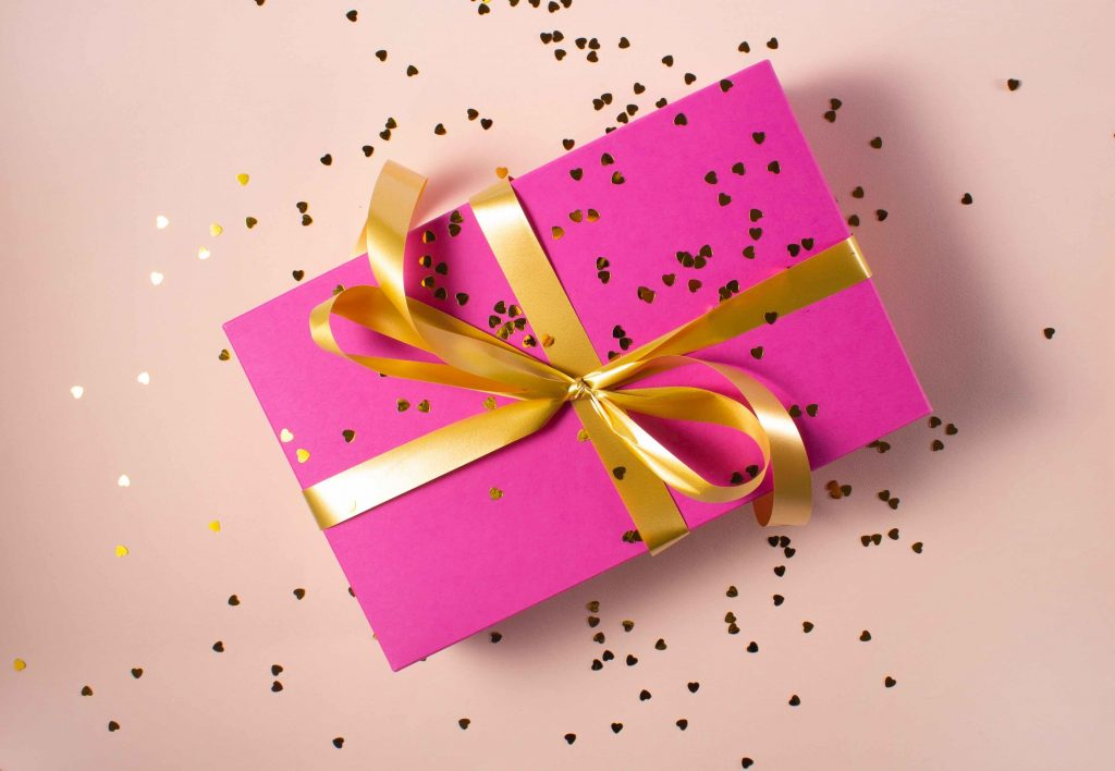 gift box with gold ribbon and heart confetti
