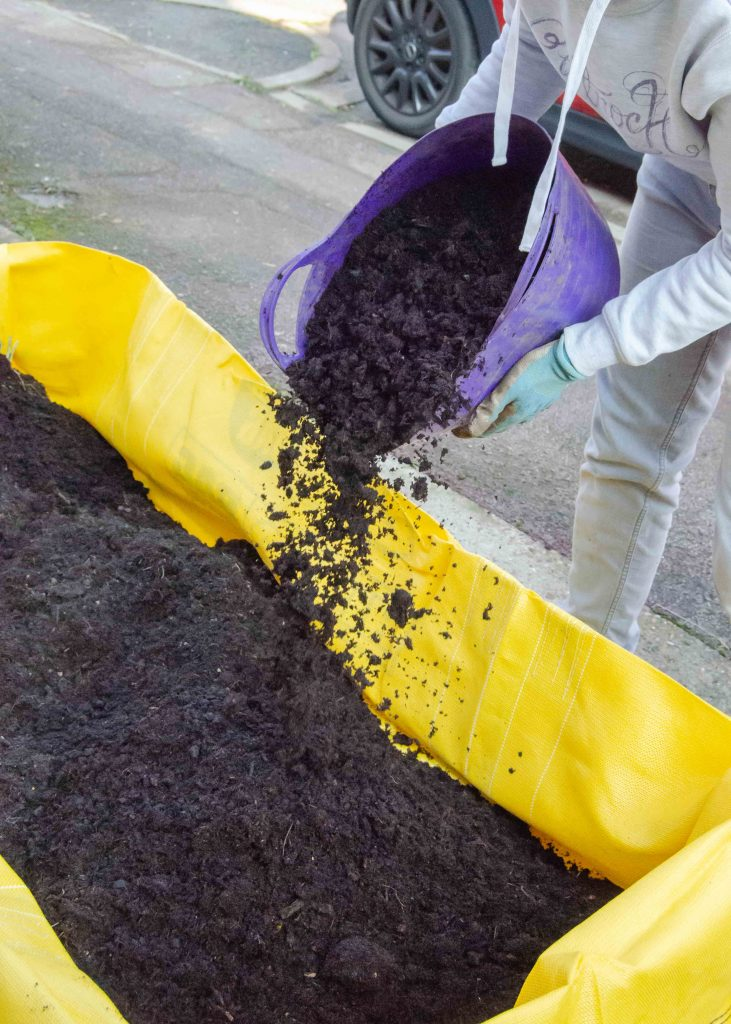 filling a skip bag with soil