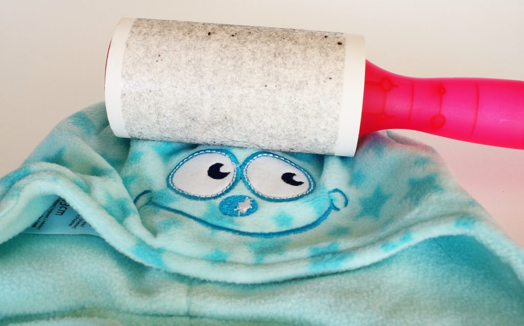 lint roller removing pet hair from clothing