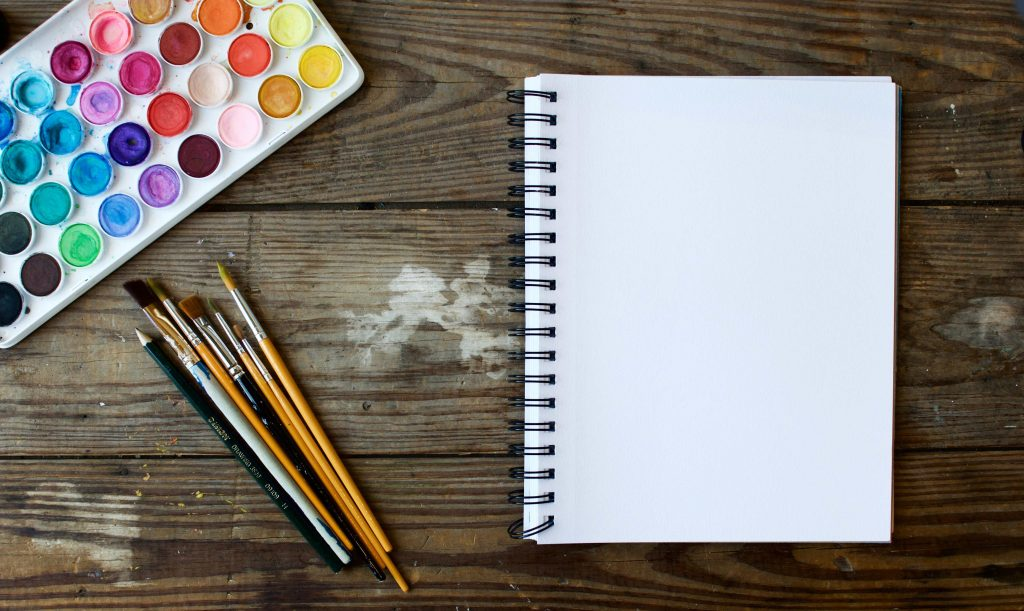 paint palette with paintbrushes and sketchpad