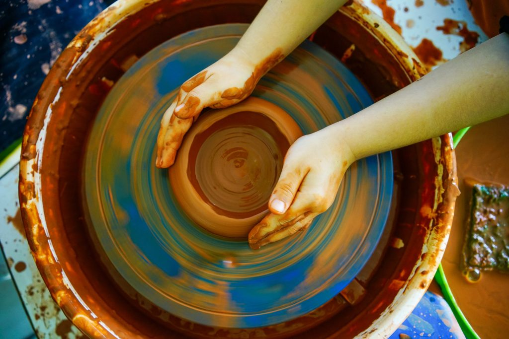 pottery wheel with hands moulding clay
