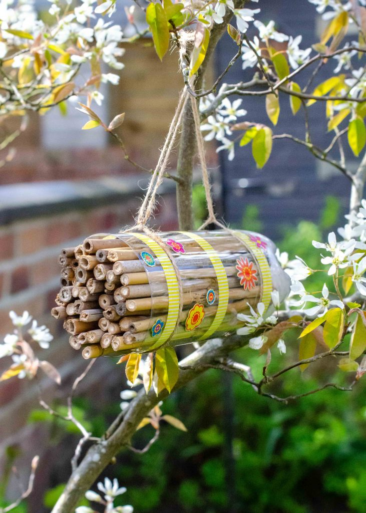 homemade bug hotel hanging in tree