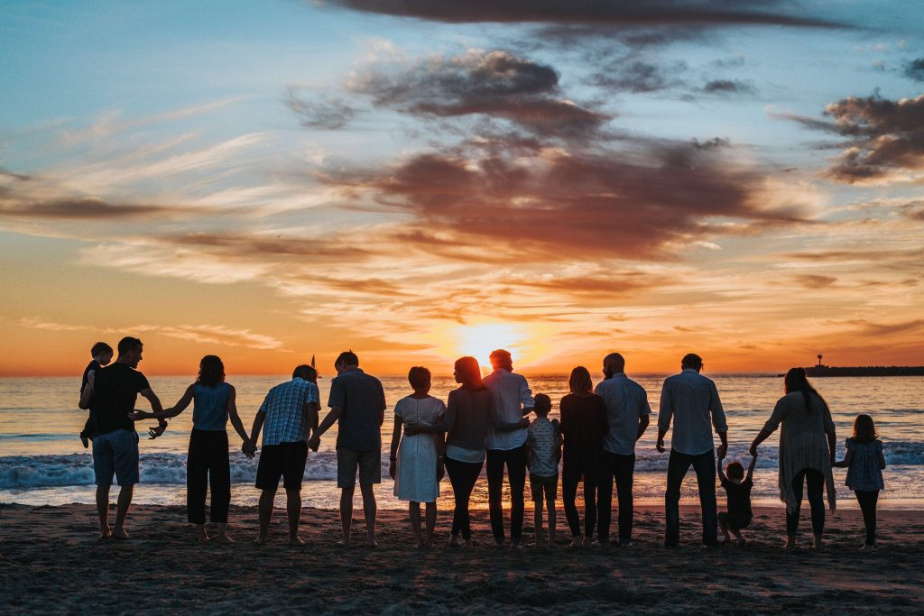 family standing on a beach at sunset