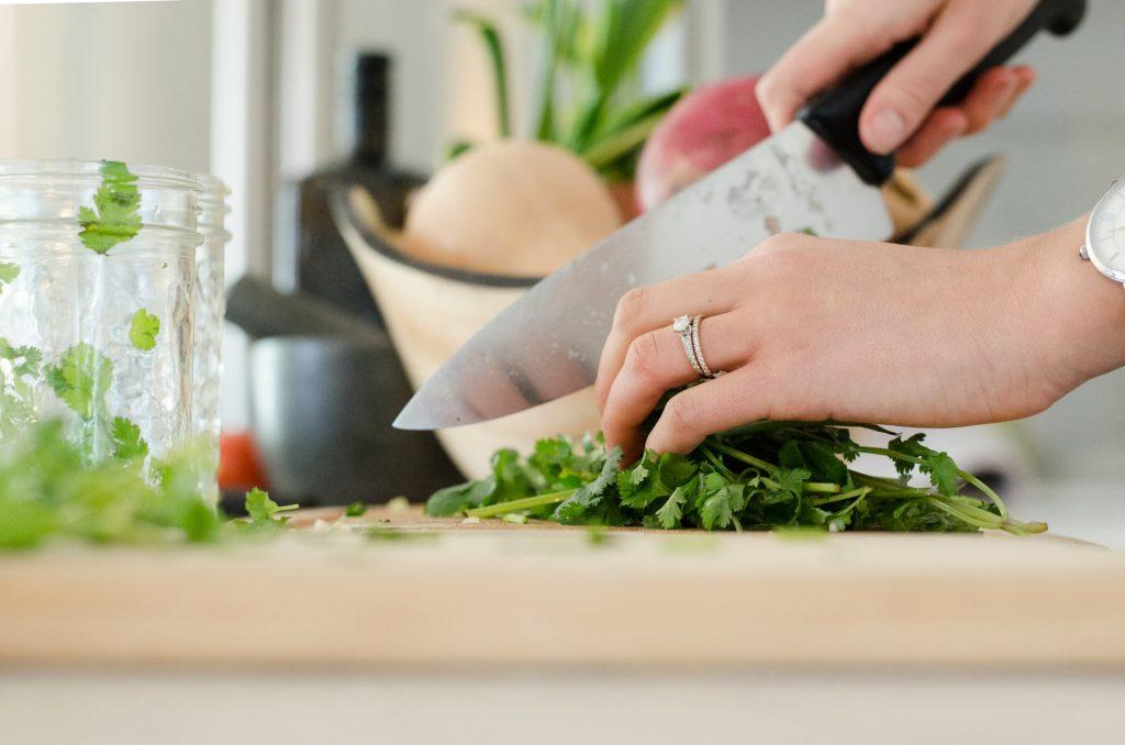 closeup of hands chopping herbs