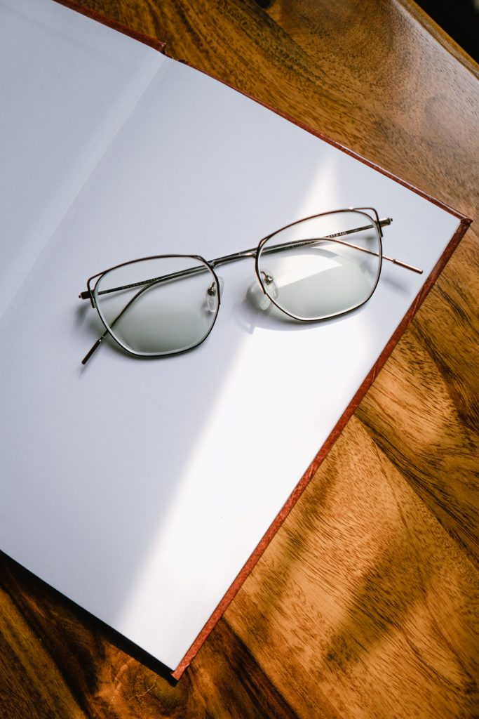 pair of reading glasses on book